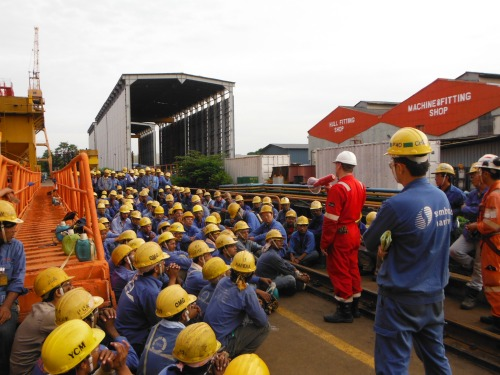 Vice President- QHSE for Helix, Wallace Robertson (red coveralls), talks to the shipyard workers in Singapore about how important safety is to Helix.